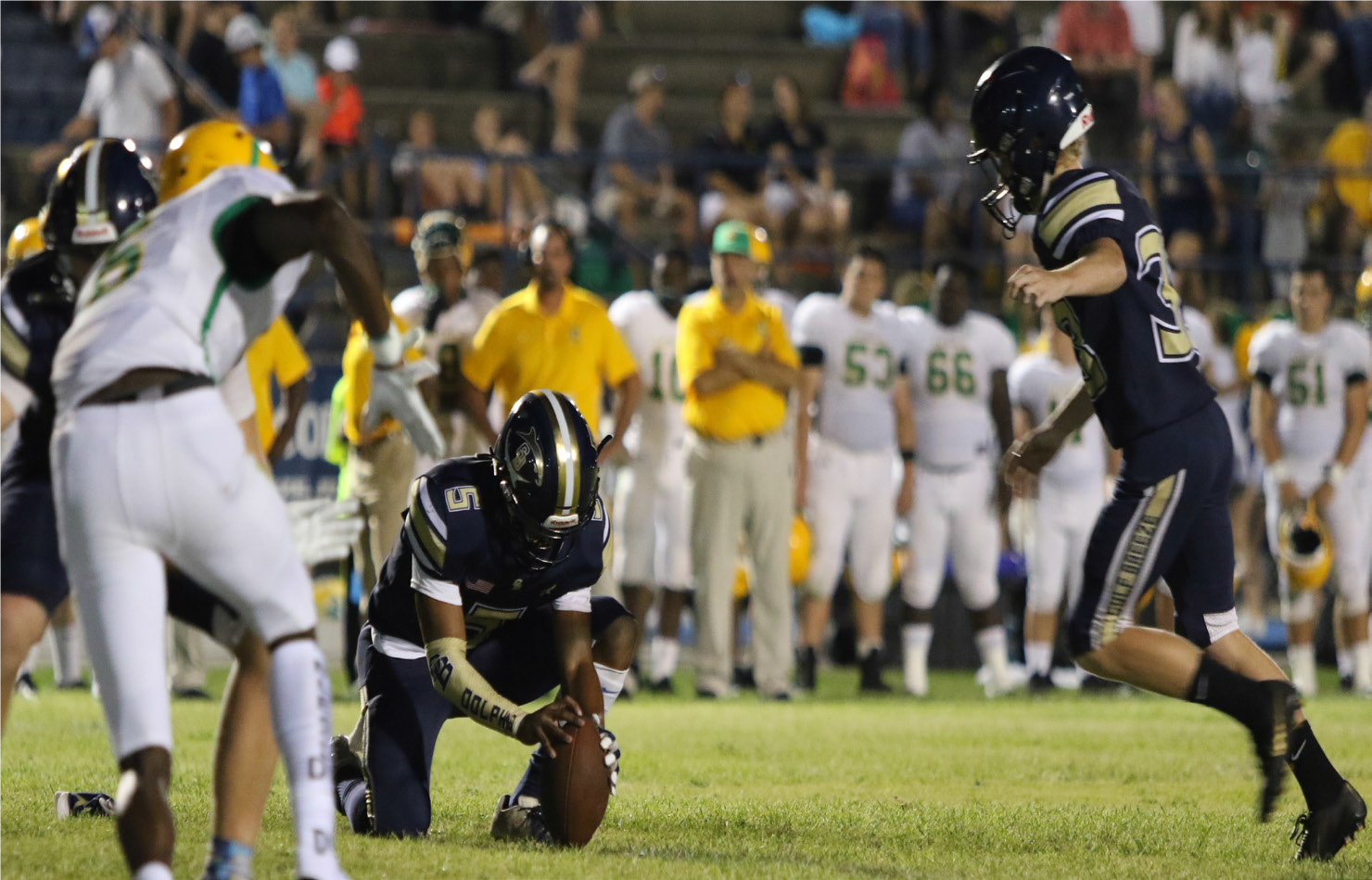 Devon Baldwin (5) holds the ball for a Dolphins kick against Catholic High School.
