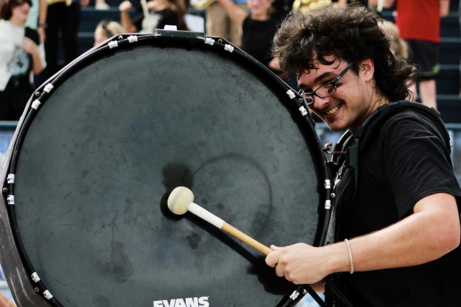 Senior Jackson Mahar plays the bass drum in the Gulf Breeze Drum Line at the first pep rally of the year