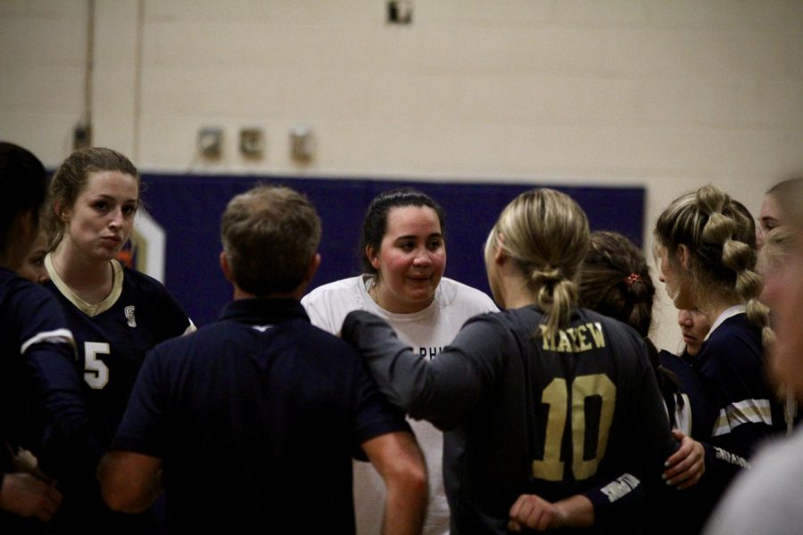 Coach Jasmine gives a pep talk to the varsity volleyball team